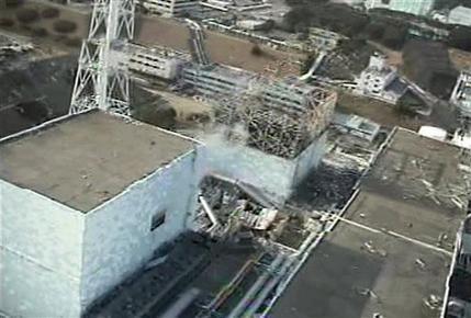 Двое работника в защитных костюмах зашли в здание реактора номер один и подключили вентиляционное