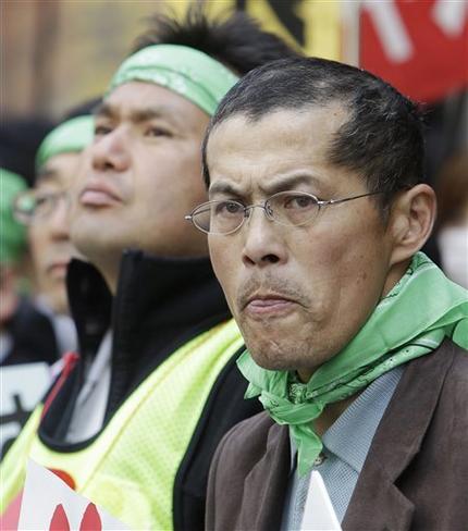 Фермеры с северо-востока Японии в зеленых банданах с плакатами