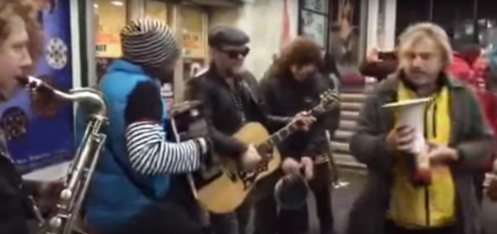 Основатель «Аквариума» в темных солнцезащитных очках с двумя своими музыкантами подошел к играющи