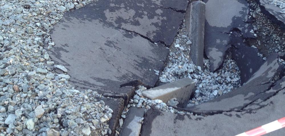 По словам начальника управления дорожного строительства, трещина находилась в прилотковой части.