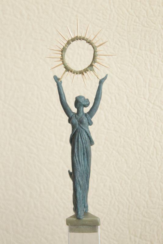 Скульптура представляет собой фигуру женщины, которая держит над головой сияющий солнечный диск.